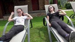 Two girl friends relaxing on park deckchairs. UHD 4K steadycam stock footage Stock Footage