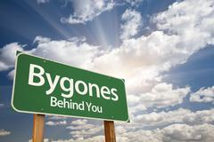 Bygones, Behind You Green Road Sign Against Dramatic Sky, Clouds and Sunburst - stock photo