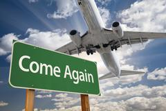 Come Again Green Road Sign and Airplane Above - stock photo