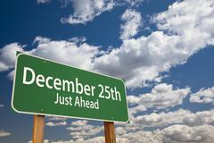 December 25th Just Ahead Green Road Sign Over Dramatic Clouds and Sky. - stock photo