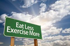 Eat Less Exercise More Green Road Sign with Dramatic Clouds, Sun Rays and Sky - stock photo