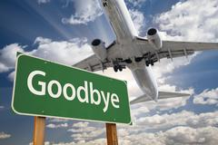 Goodbye Green Road Sign and Airplane Above with Dramatic Blue Sky and Clouds. - stock photo