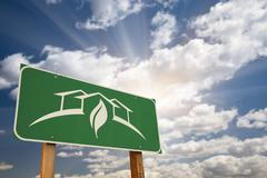 Green House Design Green Road Sign Against Dramatic Sky, Clouds and Sunburst. Stock Photos