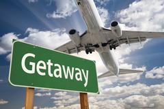 Getaway Green Road Sign and Airplane Above with Dramatic Blue Sky and Clouds. - stock photo
