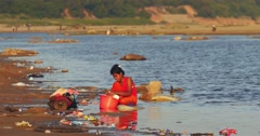 Young Burmese woman washes clothes in water of Irrawaddy river in rural Myanmar Stock Footage