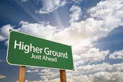 Higher Ground Green Road Sign Against Dramatic Sky, Clouds and Sunburst. Stock Photos