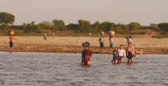 Burmese peasants on Irrawaddy river bank at sunset. Women from local village Stock Footage