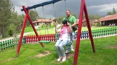 Young beautiful teenage couple is having fun on a swing. UHD 4K  stock footag Stock Footage