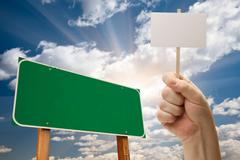 Blank Green Road Sign and Man Holding Poster on Stick Over Blue Sky and Cloud - stock photo