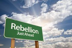 Rebellion Green Road Sign with Dramatic Clouds, Sun Rays and Sky. - stock photo