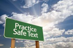 Practice Safe Text Green Road Sign with Dramatic Sky, Clouds and Sun. - stock photo