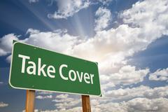 Take Cover Green Road Sign with Dramatic Clouds and Sky. - stock photo