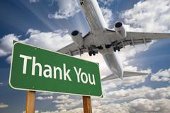 Thank You Green Road Sign and Airplane Above with Dramatic Blue Sky and Cloud - stock photo
