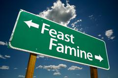 Feast or Famine Green Road Sign with Dramatic Clouds and Sky. Stock Photos