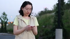 Asian woman walking and reading information on cellphone Stock Footage