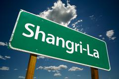 Shangri-La Green Road Sign with Dramatic Clouds and Sky. Stock Photos