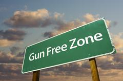 Gun Free Zone Green Road Sign In Front of Dramatic Clouds and Sky. - stock photo
