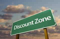 Discount Zone Green Road Sign In Front of Dramatic Clouds and Sky. - stock photo
