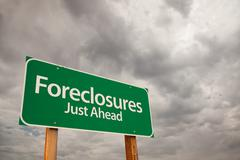 Foreclosures Just Ahead Green Road Sign with Dramatic Storm Clouds and Sky. Stock Photos