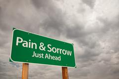 Pain and Sorrow Just Ahead Green Road Sign with Dramatic Storm Clouds and Sky Stock Photos