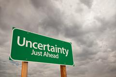 Uncertainty Just Ahead Green Road Sign with Dramatic Storm Clouds and Sky. Stock Photos