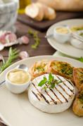 Grilled camembert with mini herbs baguettes - stock photo