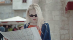 Woman tourist looking on the map trying to orientate Stock Footage