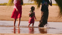 Burmese females with small kid go along the river and carry cut grass on heads Stock Footage