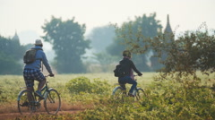 Tourist couple exploring Bagan historical site on bicycles riding on rural road Stock Footage