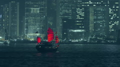 Hong Kong view at night from Victoria harbor with traditional red sail junk boat - stock footage