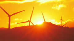 Rays of sun at sunset and rotating wind power generators - wind mill turbines  - stock footage