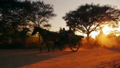 Foreign tourists sitting in horse wagon which moves along dusty roads of Bagan Stock Footage