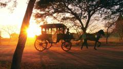 Retro transport in Burma, Bagan. Vintage horse wagon at sunset with shining sun - stock footage