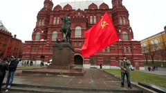 Man holds red soviet flag in front of Historical museum on Manezhnaya Square. Stock Footage