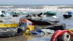 Static extreme close up of plastic garbage and trash on beach on sea background - stock footage
