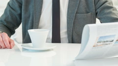Businessman drinking coffee and reading newspaper Stock Footage