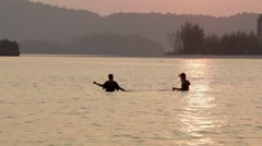 Two Thai men setting nets before low tide in Ao Nang, Thailand - stock footage