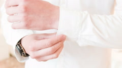 Man buttoning up sleeve - stock footage