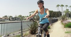Happy young woman riding bike along river Stock Footage