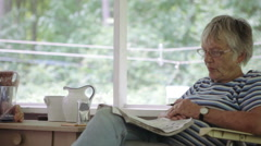 Senior Woman Solving Crossword Puzzle in Newspaper Stock Footage