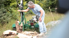 Country Senior Woman and Son Doing Chore of Cutting Wood with Woodcutter Stock Footage