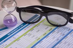 Retirement Planning with glasses and hourglass, business concept - stock photo