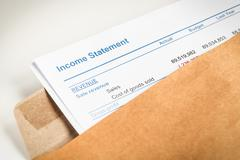 Stock Photo of Income statement letter in brown envelope opening, business concept; document