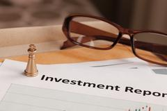 Investment Report letter document and eyeglass; document is mock-up Stock Photos