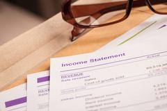 Income statement letter on brown envelope and eyeglass, business concept; doc Stock Photos