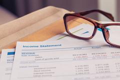 Income statement letter on brown envelope and eyeglass, business concept; doc - stock photo