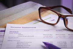 Stock Photo of Income statement letter on brown envelope and eyeglass, pen,  business concep