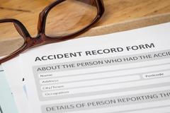 Accident report application form on brown envelope and eyeglass, business ins Stock Photos