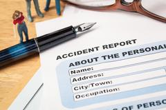 Accident report application form and pen on brown envelope and eyeglass, busi Stock Photos