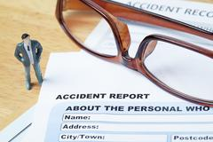 Accident report application form and pen on brown envelope and eyeglass, busi - stock photo